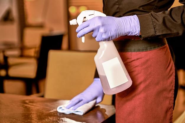 Server con un panno per pulire un tavolo del ristorante restaurant