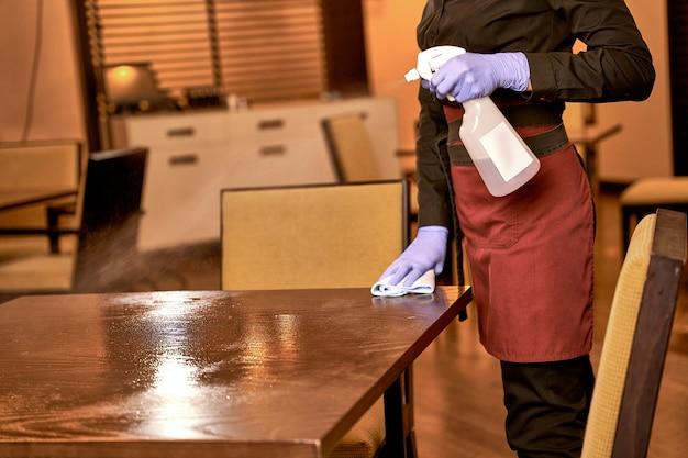 Server nel tavolo di pulizia dell'uniforme da lavoro con detergente