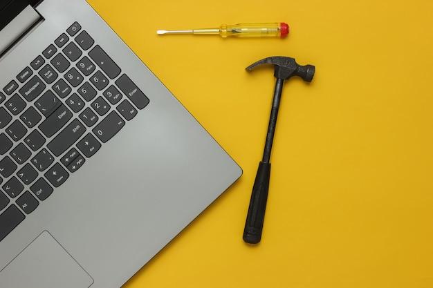 Riparazione del computer portatile del centro di servizio cacciavite e martello del computer portatile su fondo giallo