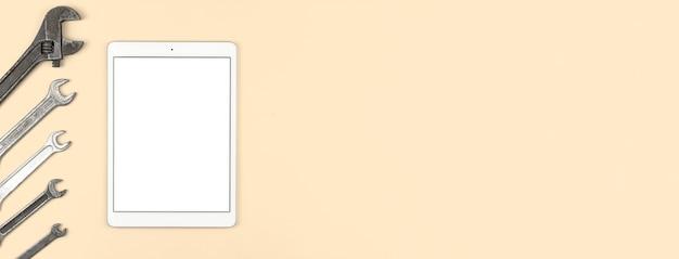 Attrezzatura di servizio e temaplet con schermo bianco vuoto tablet sul tavolo, sfondo beige, vista dall'alto, disposizione piatta e foto dello spazio di copia