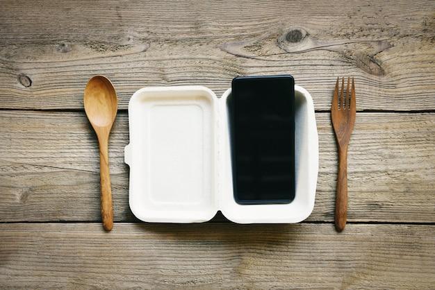 Servizio di consegna di cibo ordina online smart phone posa su cibo scatola pranzo da asporto consegna