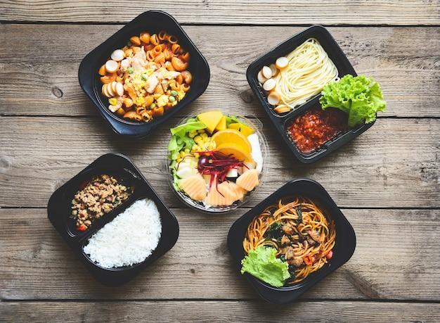 Servizio di consegna degli ordini di cibo spaghetti di riso e frutta sulla scatola di cibo, pacchetto di scatole da asporto