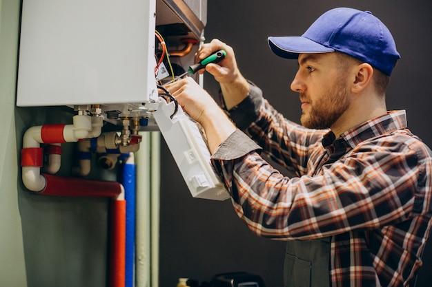 Uomo di servizio che regola il sistema di riscaldamento della casa