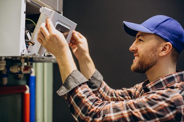 Uomo di servizio che regola il sistema di riscaldamento della casa Foto Premium