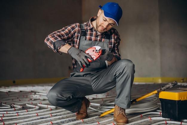 Uomo di servizio instelling sistema di riscaldamento della casa sotto il pavimento Foto Premium