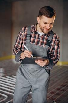 Uomo di servizio instelling sistema di riscaldamento della casa sotto il pavimento