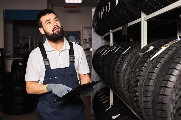Uomo barbuto del personale di servizio che esamina i pneumatici in un centro commerciale del supermercato, pensa al commercio giusto per le dimensioni della ruota, tiene in mano la tavoletta di carta, controlla