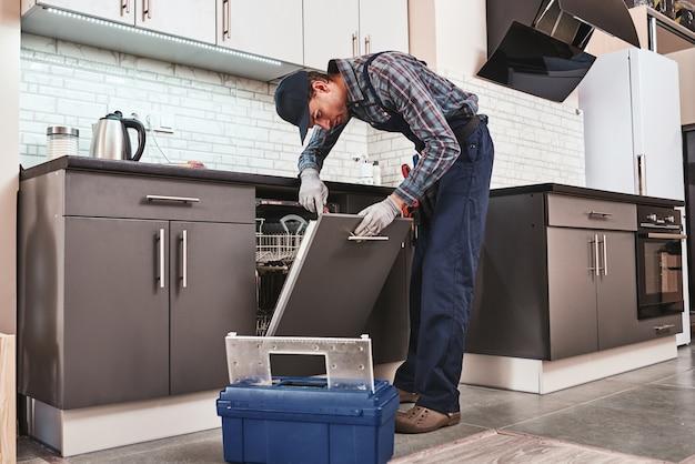 Servizio in tempo tecnico maschio seduto vicino alla lavastoviglie