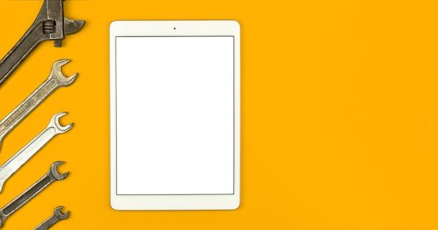 Concetto di mockup del lavoratore di servizio, schermo bianco vuoto del tablet con gli strumenti della chiave inglese sul tavolo, sfondo giallo, vista dall'alto, disposizione piatta e foto dello spazio della copia