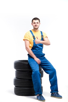 Serviceman in uniforme blu seduto su pneumatici, sfondo bianco, riparatore con pneumatici