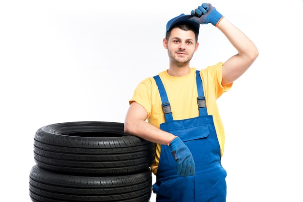 Serviceman seduto su pneumatici, bianco