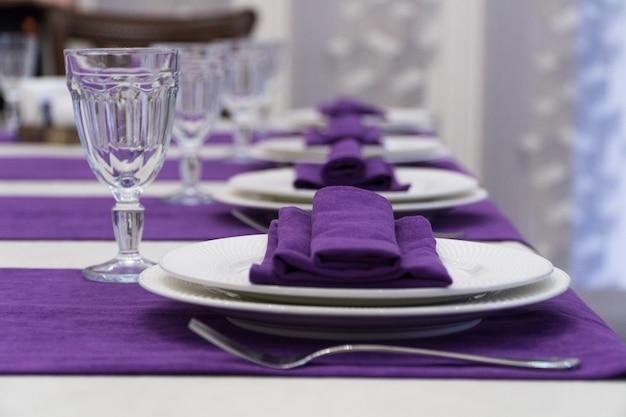 Servire il tavolo del banchetto in un lussuoso ristorante in stile viola e bianco