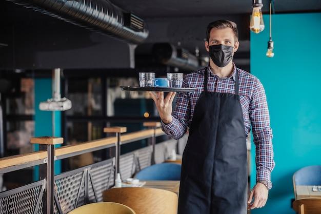 Servire caffè e acqua durante il virus corona. ritratto di un cameriere maschio in una camicia a quadri e grembiule con una maschera protettiva a piedi intorno a un caffè che porta un vassoio di caffè e acqua