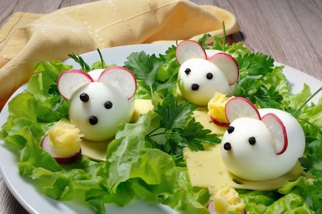 Servire uno spuntino festivo per bambini uova sode sotto forma di topi in foglie di lattuga e formaggio