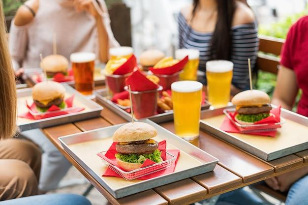 Servizio di hamburger e birre fredde al tavolo di un ristorante all'aperto con persone anonime sedute intorno al cibo e messa a fuoco selettiva su un cheeseburger