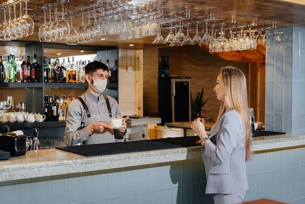 Servire un barista mascherato delizioso caffè naturale a una ragazza in un bellissimo caffè durante una pandemia