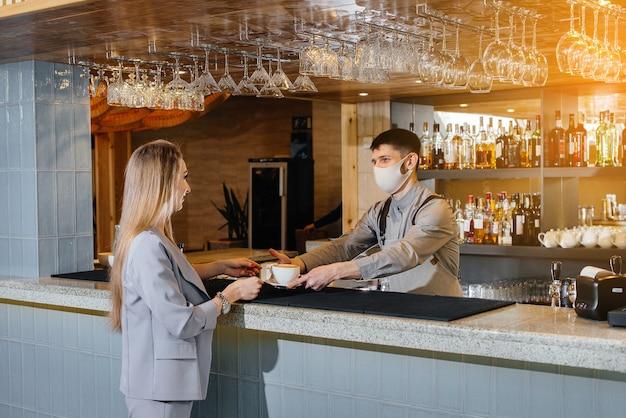 Servire un barista mascherato delizioso caffè naturale a una ragazza in un bellissimo caffè durante una pandemia.