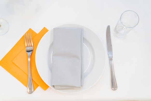 Servire tavolo piatto bianco tovaglioli forchetta con coltello e un bicchiere vuoto sul tavolo