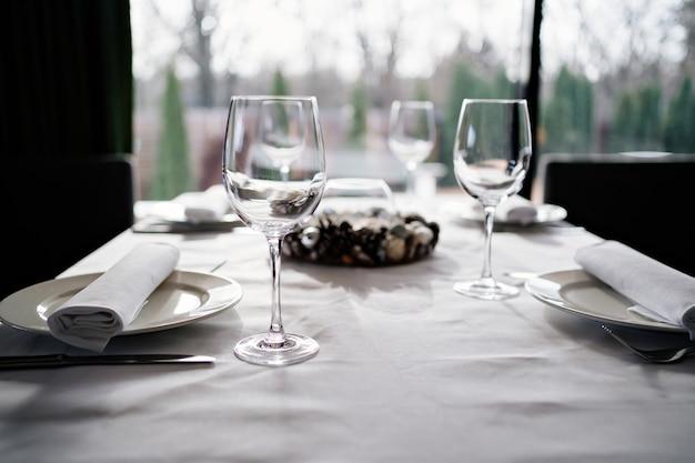 Servire la tavola. bicchieri da vino, piatti, tovaglioli e posate. design della tavola per una cena festiva. servizio in un ristorante o bar.