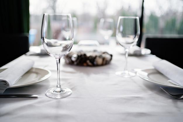 Tavolo di servizio. bicchieri da vino, piatti, tovaglioli e posate. design della tavola per una cena festiva.