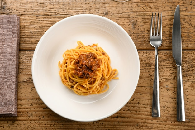Servizio di tagliolini pasta italiana con ragù di cinghiale su un piatto di ceramica bianca con posate e tovagliolo su un tavolo in legno rustico in una vista dall'alto verso il basso