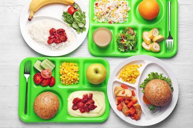 Vassoi da portata con cibo delizioso sul tavolo. concetto di pranzo scolastico