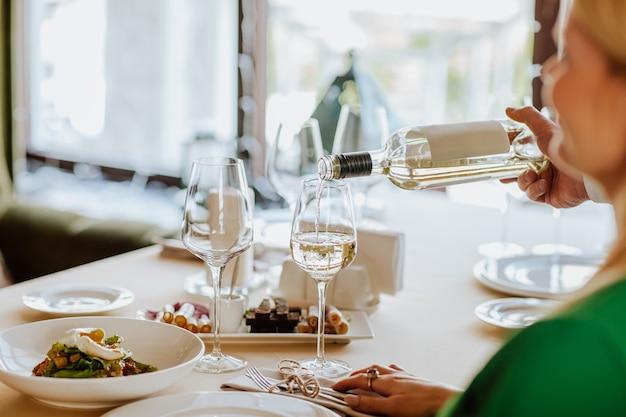 Servizio di vino bianco al cliente nel ristorante. l'attenzione è rivolta alla bottiglia e al bicchiere.