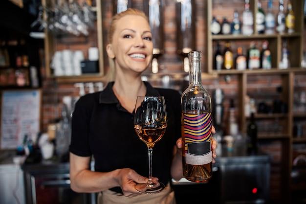 Servire il vino in cantina. intenditrice di vino femminile in un'uniforme moderna che lavora dietro il bancone. la donna tiene una bottiglia di vino in una mano e un bicchiere di cristallo pieno di vino bianco nell'altra
