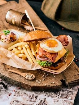 Hamburger di sesamo con pancetta, uova e patatine fritte su un tagliere di legno.