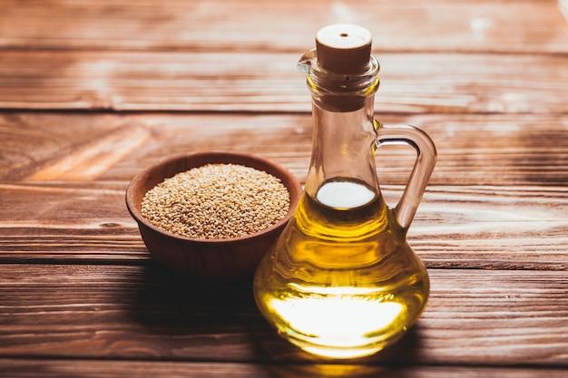 Olio di sesamo in una bottiglia di vetro con sughero e semi di sesamo in una ciotola di legno