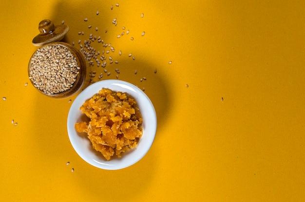 Semi di sesamo in pentola di creta con jaggery in una ciotola su sfondo giallo