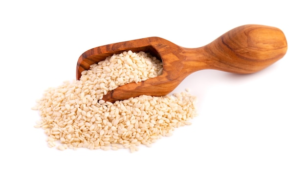 Semi di sesamo in cucchiaio di legno, isolato su bianco. semi di sesamo secchi biologici.