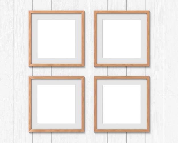 Set di 4 mockup di cornici quadrate in legno con un bordo appeso al muro. base vuota per foto o testo. rendering 3d.