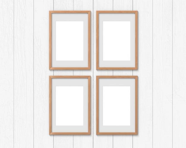 Set di 4 mockup di cornici verticali in legno con un bordo appeso al muro. base vuota per foto o testo. rendering 3d.