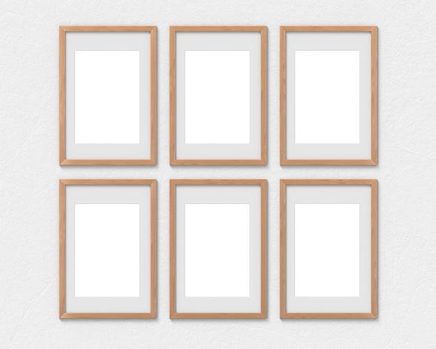 Set di 6 mockup di cornici verticali in legno con un bordo appeso al muro