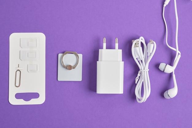Un set di accessori per smartphone, caricabatterie, cuffie, tenendo un anello, adattatori per schede sim su uno sfondo viola spazio copia vista dall'alto