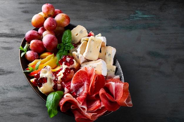 Una serie di antipasti per vino, prosciutto, peperoni, formaggio, uva, pesche su un piatto da vicino.