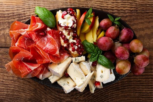 Una serie di antipasti per vino, prosciutto, peperoni, formaggio, uva, pesca su una vista dall'alto del piatto.