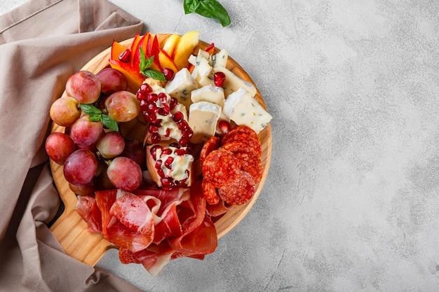 Una serie di antipasti per vino, prosciutto, peperoni, formaggio, uva, pesca su una tavola di legno vista dall'alto.