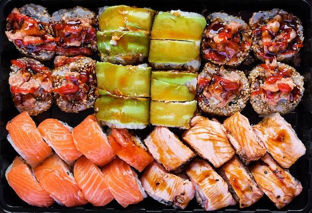Set di cibo asiatico. sushi, rotoli su sfondo nero. vista dall'alto, sopra