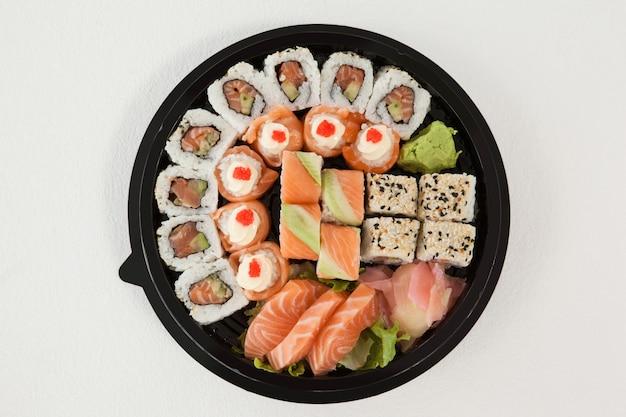 Set di sushi assortiti tenuti in una scatola nera rotonda
