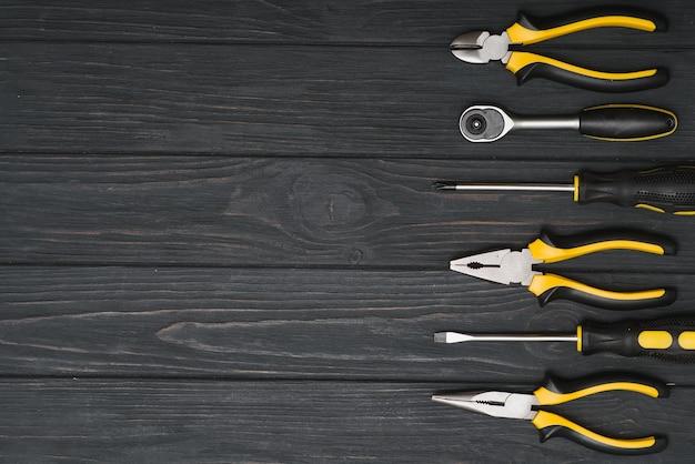 Set di falegnameria di lavoro assortiti e attrezzi da fabbro su uno sfondo di legno scuro con spazio di copia.