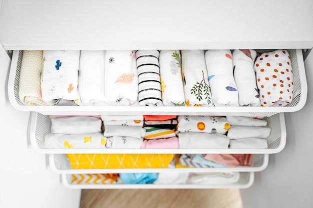 Set di body per neonato per bambina e bambino appesi su grucce nell'armadio bianco. maternità, pulizia del guardaroba dei bambini a casa. concetto di moda minimale.