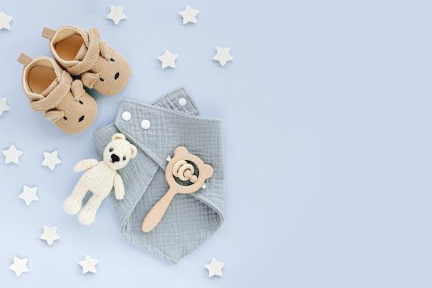 Set di scarpe per bambini, giocattoli e accessori su sfondo blu. roba da neonato alla moda. disposizione piatta, vista dall'alto