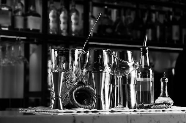 Set di accessori da bar per la preparazione di cocktail, situato sul bancone, dietro c'è una scaffalatura con liquori e alcolici forti. tecnica mista