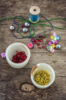 Set di perline in pile sul tavolo in legno con strumenti per cucito.