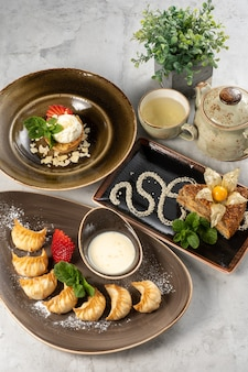 Una serie di bellissimi dessert e una tazza di tè verde con una teiera. canederli dolci di gyoza con fragole fresche, crostata di mandorle con gelato e torta arrosto esterhazy con physalis e menta