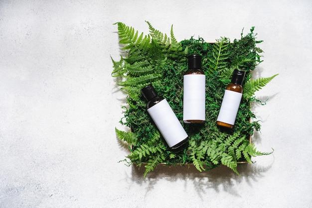 Set di prodotti di bellezza in confezione regalo con muschio e felce su sfondo di cemento bianco, vista dall'alto