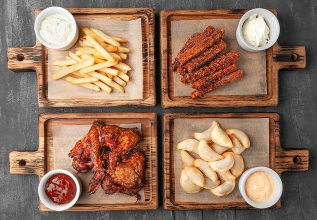 Set di snack alla birra. composto da ali di pollo, patatine fritte, bastoncini di carota caldi e gnocchi fritti con salse. . servito su tavole di legno. vista dall'alto. sfondo grigio cemento.