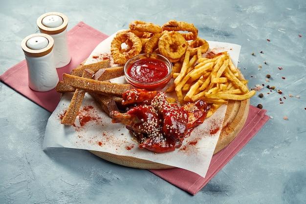 Set di crostini di birra snack, ali di bufalo, patatine fritte, anelli di cipolla su una tavola